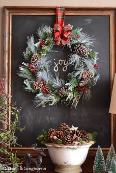Rustic Christmas. Wreath on top of chalkboard (or mirror like the one in our dining room) hung by a plaid ribbon.