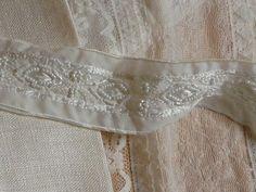 Herrliches edles Band in creme.  Auf dem Band befindet sich eine Perlenstickerei im grafischen Muster.  Die Perlenstickerei ca. 1,7 cm hoch.  Ein Rapport ist ca. 4,5 cm breit.  Über und unter der Perlenstickerei befindet sich ein Satinband.  Das Satinband ist ca. 0,5 cm hoch.  Die ganze Borte ist ca. 5 cm breit.  Das Band ist sehr ausgefallen.      Das ausgefallene Band ist vielseitig einsetzbar z.B. an Armabschlüssen, Säumen, Halsausschnitten aber auch an Taschen oder Kissen.