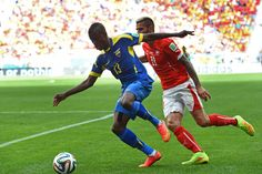 Enner Valencia of Ecuador dribbles past Valon Behrami of Switzerland with the help of black kinesiology tape on his quad