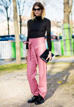 Veronika Heilbrunner wears a black turtleneck, high-waisted pink belted trousers, a black clutch, and Dr. Martens boots with cat-eye sunglasses