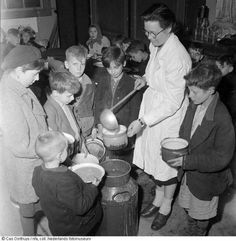 1944 - 1945. Volunteer at a soup kitchen in Amsterdam distributes soup among children during