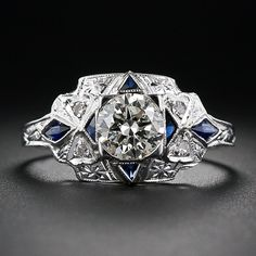 Art Deco Ring A bright European-cut diamond, weighing just one point shy of a carat, is dramatically set off by four deep-blue synthetic sapphires (original to the ring and the period) set at the cardinal points. The shoulders of the ring are adorned with a diamond-set bowtie motif leading to a diamond-shape synthetic sapphire and a decoratively engraved upper ring shank. Die-struck and hand finished in 18 karat white gold - circa 1930s.