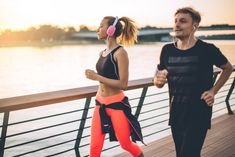 Young couple enjoying in their workout together. They are wearing sport clothing. Enjoying in beautiful day by the river.