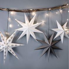 Fyra adventsstjärnor STRÅL i olika mönster och färger hänger på en gren tillsammans med STRÅLA LED-ljusslinga.