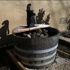 Wine barrel water feature.  It was so much easier to construct than we thought and fun addition to our yard!  -wine barrel (free for us-had the barrel) -plastic flower planter ($10-less than pond liner) -fountain/pond pump ($15-harbor freight tools) -decorative water hand pump ($22-harbor freight tools) -pond tubing