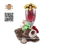 Incluye oso de peluche abrazando un jarrón de vidrio decorado con besitos de chocolate Hershey´s, petalos de rosa, 6 rosas y 16 chocolates Ferrero Rocher. Incluye lazo y tarjeta para anotar su mensaje.