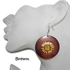 Flower earrings, real flower earrings, dried flower earrings.  This wooden earring is a wonderful way to feel the nature in your accessories. This earring is a round lightweight wooden earring surrounding a the dried flower pedals accentuated by a natural looking center. The flower pedals are protected under a clear gem like center. This allows the earring to be protected and yet have the feel of nature we all look for. This earring is cheap at only $1.00 each pair.