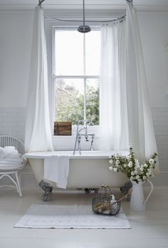 Love this all-white bathroom with roll-top bath, white floors, chair, fluffy towels and flowers. It has all the ingredients to make you feel that you have a spa at home. More ideas on how to make your bathroom a 'spathroom' on W&W.