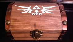 """It's dangerous to go alone"" whatever you decide to store in this chest will surely help you through your adventures! [[Hand painted, stained, and upholstered]] The elegant Triforce bird is the outside centerpiece, boldly adorning the top of the chest, while the three symbols that define the meaning of the Triforce charmingly adorn the inside, giving anyone who opens it for the first time a pleasant surprise. The ""Zelda Treasure Chest"" has also been equipped with a soft, lovely wool fabric."