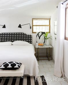 In this bedroom, a polka-dot headboard contrasts with crisp white bedding and plays off the bold black and white striped rug.   Photographer: Tara Sgroi   Designer: Barbara Sgroi
