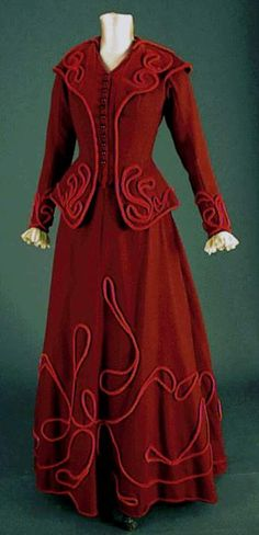 Set jacket tailor-fitted, slightly longer front and many cutouts, V-neckline with shawl collar cut into two half-circle without whales, with extra high collar, just by closing of staples and small buttons decorative rod translucent red plastic, Basque able semicircular the back part, long and lined with unbleached adjusted antique lace cuffs sleeves, stand-up collar cape with separate arriving at the waist.