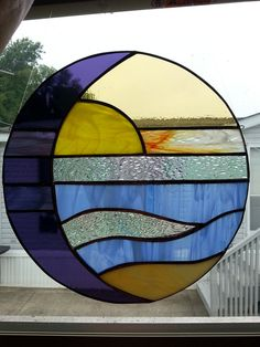 Stained glass window panel is created using purple, iridescent purple, blue wispy, cream, yellow wispy, orange gecko, crystal iridescent, and amber stained glass. finished in a copper patina finish ready to hang in a window, garden stake or wall. measures 10.25