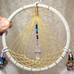 """Light and energizing, this darling hand-crafted dreamcatcher features a web in a teepee-shape! Suspended in front of its """"door"""" is a Chakra Los Dreamcatchers, Photos Booth, Medicine Wheel, Sun Catcher, String Art, Wind Chimes, Chakra, Creations, Weaving"""