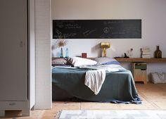 Creëer extra opbergruimte met een lange houten plank achter het bed. Zo kun je al jouw benodigdheden snel en gemakkelijk opbergen.