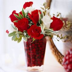 Cranberry Christmas Flowers Fill a vase half full of cranberries and fresh water and insert a floral arrangement, such as roses and holly leaves. Add more water and cranberries to hide the stems of the holiday mantel decoration.