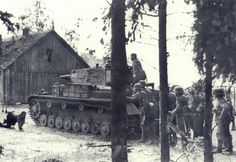 Under the protection of a Pz.Kpfw.IV Ausf.B/C a group of soldiers take cover during intensive fighting inside a Lithuanian village on 26 June 1941.