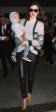 Leather leggings and high-shine heels are standard airport fare for superfly mom Miranda Kerr, who pares down the sexy style for an LAX appearance with a simple tee and cozy cardigan.