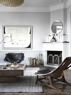 Minimalist apartment with herringbone floors, crown molding, and structural armchairs