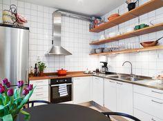 Urządzona w typowo skandynawskim stylu zabudowa kuchenna została zaprojektowana bez szafek górnych. Zastępują je długie drewniane półki, będącym ciepłym akcentem stylistycznym. Fot. Stadshem.