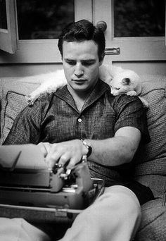 A young Marlon Brando at his typewriter with his editorial assistant...or from the look, it might be his critic...draped over his shoulder.