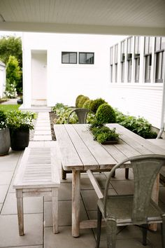 The outdoor eating area is decorated with rustic whitewashed furniture