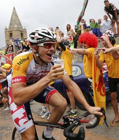 Lotto-Belisol team rider Adam Hansen of Australia drinks a glass of beer as he climbs the Alpe d'Huez mountain during the 172.5km eighteenth stage of the centenary Tour de France.