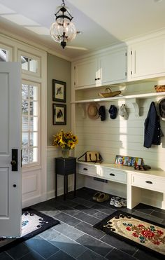 Traditional style Mudroom design with Slate Floor, entry bench, ivory/cream walls, and coat hooks