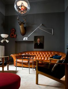 Grey walls, brown leather couch, oil portrait painting, modern lighting, high tea table
