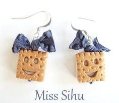 Gourmandes, petites boucles d'oreilles avec un biscuit carré MIAM fourré blanc en fimo.   Noeud élastique fimo bleu jean.  Boucles idéales pour une...