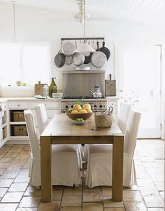 Chairs and table are from Crate and Barrel. To create even more warmth in the room, Pearson and her husband, chiropractor Brett Laymance, picked out reclaimed French terra-cotta tiles one by one for the floor, which brilliantly reflects the Ojai light. The stove is Thermador.   - HouseBeautiful.com