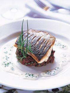 Serves guests these fillets of sea bass on provencal lentils with a creamy chive sauce; an impressive dish that isn't too difficult to make.