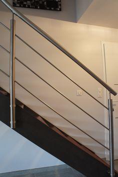 Rampant d'escalier avec main courante en tube inox brossé et remplissage en rond d'inox. Cette rampe vient habiller l'escalier AURELIANI tout en légèreté.