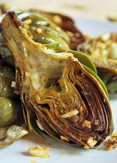 Estas alcachofas asadas son una exquisitez, la alcachofa se complementa de maravilla con un toque ácido del limón y la riqueza y profundidad del ajo con muy pocos ingredientes hacen una comida para chuparse los dedos literalmente.