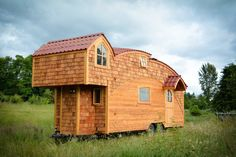 This is the MoonDragon tiny house. It's designed and built by Zyl Vardos in Olympia, Washington. The home features a handmade dutch-style door and a beautiful roofline. Inside, you'll f…