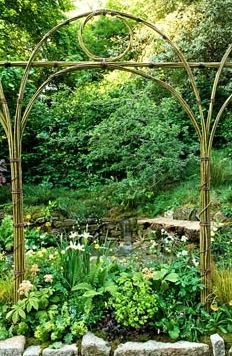 Natural arch above border of Iris Trollius, Rodgersia and Alchemilla mollis, Corylus maxima 'Purpurea', Primula chungensis. Small waterfall. The 'Music on the Moors' garden - Gold medal winner at RHS Chelsea Flower Show 2010
