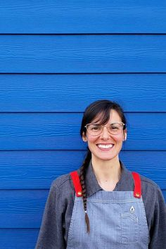 Pluvio Restaurant and Rooms is a boutique hotel in Ucluelet on Vancouver Island, Canada 🇨🇦 The team wear our Henry Bib Aprons in Pebble with their bold Red Straps standing out vibrantly against the backdrop of their beautiful blue building ❤️💙 | Restaurant Design | Waiter Uniform | Restaurant Aprons