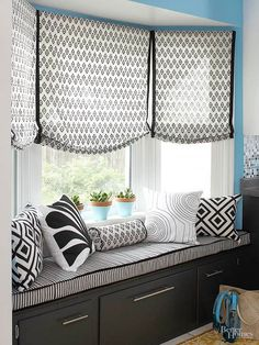 There's nothing cozier than a window seat. Dressed in pretty coordinating graphics, the built-ins gains even more charm. Black-and-white fabrics in varying scales of patterns suit pillows, an upholstered cushion, and a trio of Roman shades. Embracing scale and the linear bench seat, the shade fabric is a medium-size diamond pattern bordered by a bolder black stripe.