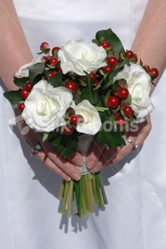 Beautiful flowers in a classic Christmas bridesmaid bouquet. Perfect for an festive Christmas themed wedding. Real touch white rose and red berry bridesmaids wedding bouquet. Hand tied bouquet with luxury fresh touch roses and festive berries. Stems wrapped in an white and gold Christmas ribbon. Bouquet finished off with offset crystal pins throughout.