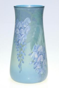 Beautifully executed Rookwood Vellum glaze vase with wisteria decoration done in 1925 by Ed Diers. Three large and nicely detailed clusters of flowers descend from the rim. Marks include the Rookwood logo and date, shape number 1023 C and the incised monogram of the artist. There is also an artist incised V on the bottom. Height 10 3/8 inches. Uncrazed and very clean.