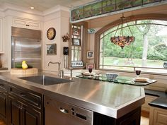 Charming kitchen featuring custom stainless steel counter by Focal Metals