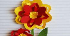 1.Z żółtego i czerwonego papieru wytnij kwadraty - większy i mniejszy. 2.Kwadrat złóż na pół, następnie jeszcze raz na pół i po raz trzeci, tak, żeby powstał trójkąt. 3.Przytnij brzeg trójkącika tak, żeby był on zaokrąglony. 4.Rozłóż kwiatek. Co drugi płatek natnij nożyczkami. 5.Uformuj płatki kwiata, by nie były płaskie. 6.W taki sam sposób zrób kwiat innego koloru, tylko mniejszy. Sklej je ze sobą.   Przyklej kwiaty do tekturki (dobrze będą wyglądały na falistej)