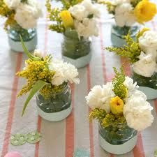 baby food jars dipped halfway in white paint and filled with flowers for a baby shower.