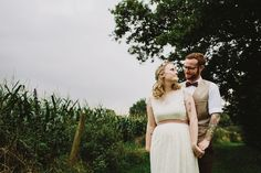 Bride wears a capped sleeve lace dress with pink sash   Photography by http://www.lukehayden.co.uk/