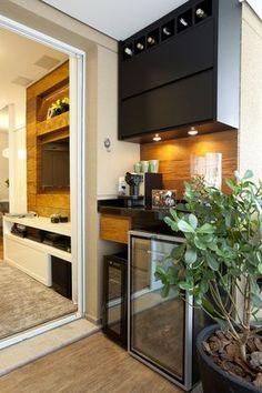 A adega e uma pequena pia fazem as vezes de cozinha. A identidade visual do acabamento de madeira está de acordo com o painel de TV da sala.  Foto: Beatriz Quinelato Arquitetura