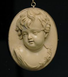 An antique Lava cameo brooch, circa 1860, the finely modeled three-quarter profile cherub carved in lava stone with floral festoon, and framed in a 9ct rose gold mount with a pin fitting.