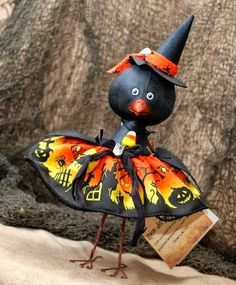 """Resin crow doll with satin and velvet bat print skirt, spider print headband with leather bat handcut applique, lampwork glass bat necklace, candy corn ribbon with metal candy corn charm,stands 6"""" on wired legs."""