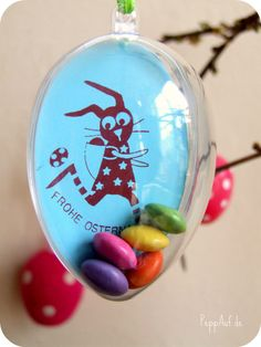 Clear plastic Egg with stamped Easter pic or scene inside- add a little candy but don't cover your pic inside. Add a string on your clear plastic egg if there's a hole and hang on branches. Step-by-step pic tutorial.