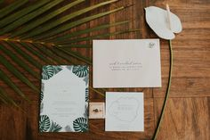 Tropical leaf stationary on wood table with anthurium and palm greenery. Tropical Wedding Reception, Kauai Wedding, Destination Wedding Inspiration, Tropical Leaves, Wedding Stationary, Cards Against Humanity, Invitations, Floral, Style Blog