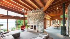 Architect Christopher Simmonds has designed the Muskoka Cottage in Muskoka, Ontario, Canada.  wood beamed ceiling, glass walls, stone fireplace, stone tile floors, clean modern easy natural