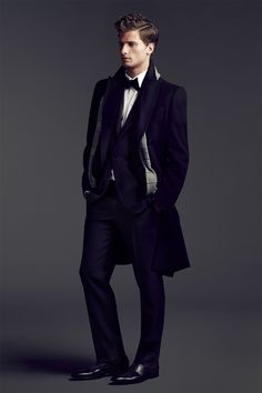 3/4 angle, standing, hands in pockets, slouchy pose // bow tie, curly hair, long coat, scarf, dress shoes, formal